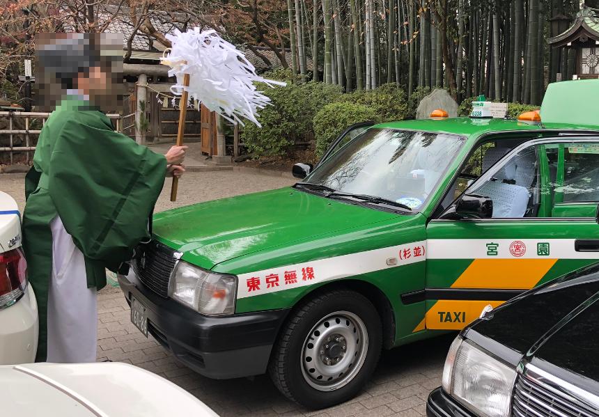 ドアを開いたタクシーに向かい大麻(おおぬさ)を振るう神職の写真